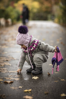 Young girl outdoors, wearing knitted suit, collecting autumn leaves - CUF07922