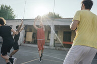 Friends on basketball court playing basketball game - CUF07970