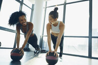Two young women working out in gym, using gym equipment - ISF01728