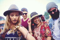 Four young adult friends in fedoras dancing at festival - ISF01761