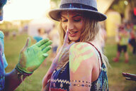 Young woman with green handprint on shoulder and boyfriend chalked hand at festival - ISF01773