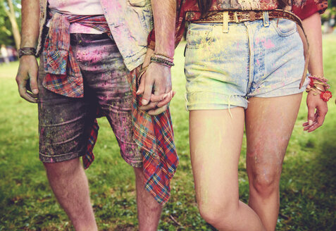 Waist down view of young couple covered in coloured chalk powder at festival - ISF01776