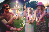 Young adults covered in coloured chalk powder holding sparklers at festival - ISF01785