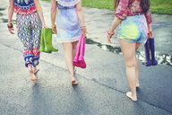 Waist down view of young women walking barefoot at festival - ISF01788