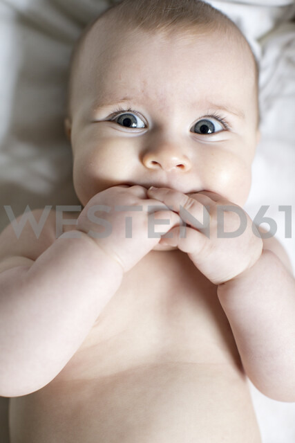 Portrait of baby girl, fingers in mouth, overhead view - ISF01893