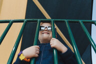 Portrait of boy wearing sunglasses looking through railings smiling - ISF01908