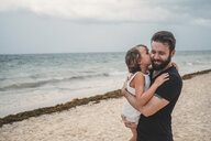 Father kissing daughter on beach, Cancun, Mexico - ISF01917