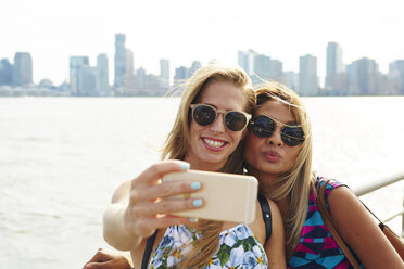 Two women taking smartphone selfie on waterfront with skyline, New York, USA - ISF01944