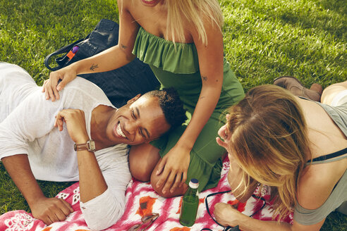 Three adult friends laughing on picnic blanket in park - ISF01953