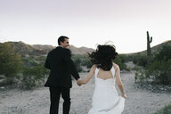 Bride and groom in arid landscape, holding hands, running, rear view - ISF02022