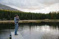 Father standing on wooden pier beside lake, holding young son - ISF02046