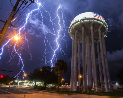 Spectacular lightning bolt with simultaneous branches strikes Cocoa, Florida, amid power lines near the city's water tower - CUF08122