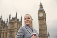 Portrait of mid adult woman holding coffee cup, Houses of Parliament in background, London, England - CUF08260