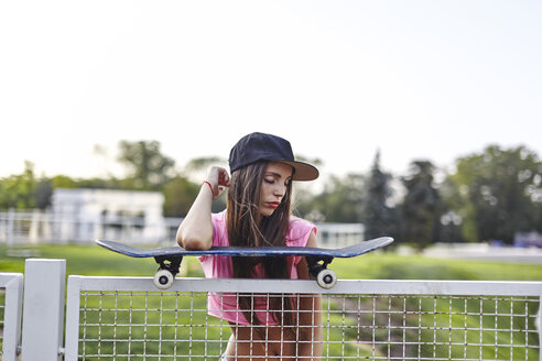 Young woman balancing skateboard on metal fence, elbow on skateboard - CUF08275