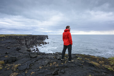 Man enjoying view on clifftop, Reyjanes, Iceland - CUF08314