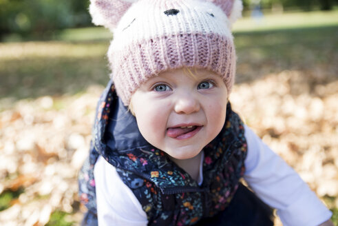 Portrait of female toddler with tongue out in park - CUF08329