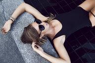Woman lying half-submerged in pool - CUF08353