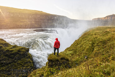 Hiker watching waterfall, Gullfoss, Iceland - CUF08356