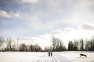 Children on snow-covered path, calling their golden retriever, Lakefield, Ontario, Canada - CUF08455
