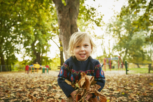 Girl playing in autumn leaves - CUF08506