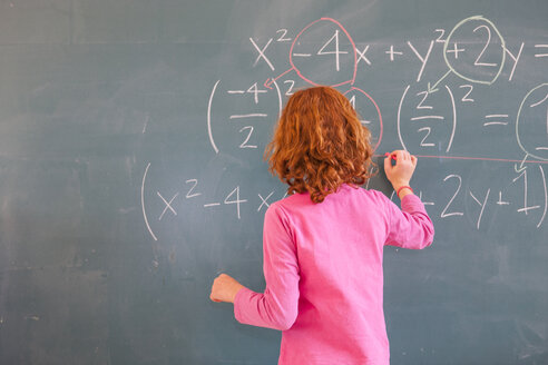 Rear view of primary schoolgirl answering equation on classroom blackboard - CUF08584