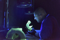 Worker using ultra-violet light to test for cracks in components in precision casting factory - CUF08641