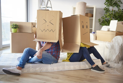 Young couple at home, wearing cardboard boxes on heads, faces drawn on boxes - CUF08665