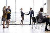 Businesswoman and man shaking hands by office window - CUF08692