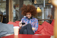 Woman at coffee shop using mobile phone - CUF08767