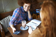 Friends with smartphone relaxing in cafe - CUF08776