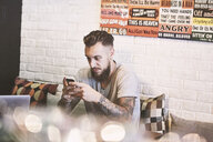 Young male hipster in cafe looking at smartphone, Shanghai French Concession, Shanghai, China - CUF08848