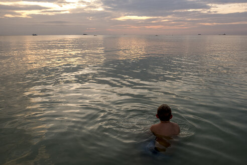 Thailand, boy swimming in the at sunset - MMIF00071