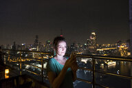 Thailand, Bangkok, portrait of woman standing on roof terrace by night using cell phone - MMIF00074