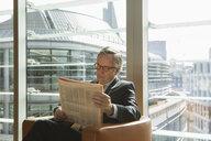 Businessman in coffee area in office, London, UK - CUF08937