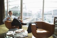 Businessman in coffee area in office, London, UK - CUF08940