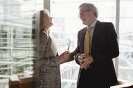 Businessman and businesswoman in coffee area in office, London, UK - CUF08952