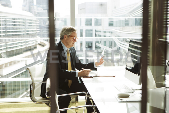 Businessman reading and analysing report, London, UK - CUF08979