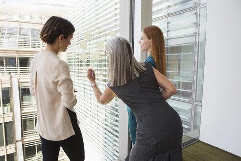 Businesswomen brainstorming ideas on glass window - CUF09021