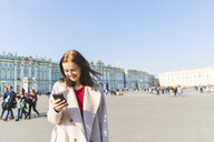 Russia, St. Petersburg, young woman using smartphone in the city - WPEF00254