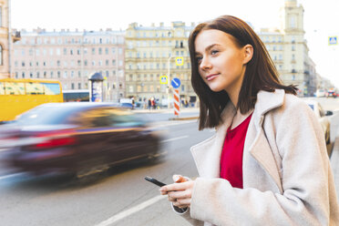 Russia, St. Petersburg, young woman using smartphone in the city - WPEF00260