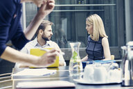Businesswoman and man having discussion at boardroom table - CUF09174