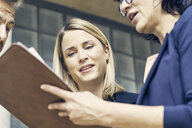 Close up of businesswomen and man discussing paperwork in office - CUF09195