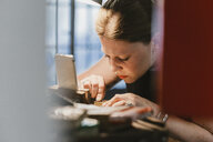 Female jeweller engraving metal at workbench - CUF09228