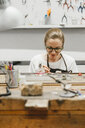 Female jeweller working with miniature hand tool at workbench - CUF09246