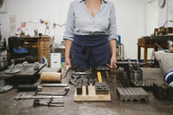 Mid section of female jeweller laying out hand tools at workbench in jewellery workshop - CUF09270