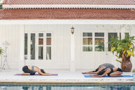 Two women and a man practicing yoga at the poolside - MOMF00415