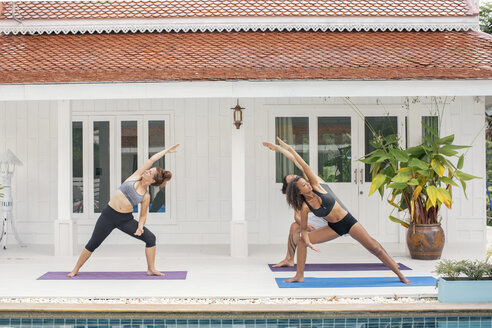Two women and a man practicing yoga on terrace - MOMF00418
