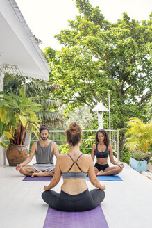 Two women and a man practicing yoga on terrace - MOMF00424