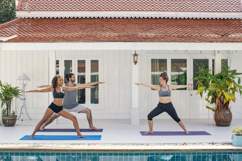 Two women and a man practicing yoga on terrace - MOMF00427