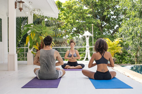 Two women and a man practicing yoga at the poolside - MOMF00430